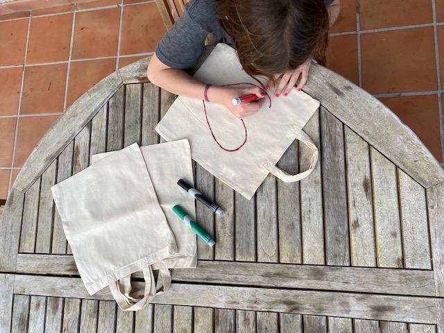 Une enfant dessinant sur un tote bag un grand coeur rouge sur une table en bois pendant le confinement